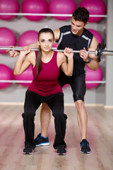 Male Gym Instructor Helping Woman Carrying Weights