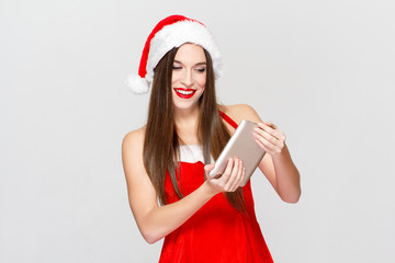 Happy woman in christmas outfit holding tablet