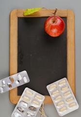 Tafel mit Medizin und Apfel