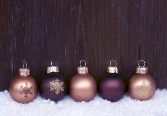 Weihnachtskugeln vor dunklem Holz