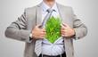 Businessman showing grass under his shirt