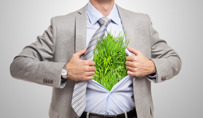 Businessman showing grass under his shirt