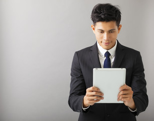 young smiling businessman watching the tablet pc