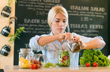 Young caucasian woman making salad