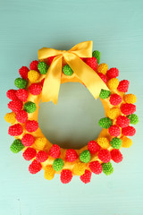 Beautiful wreath of candies on wooden background