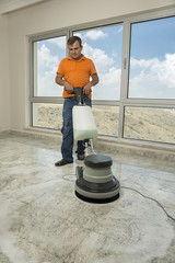 Manual worker cleaning the floor with buffer machine.