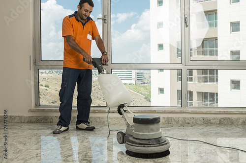 Worker wearing uniform cleaning marble floor with buffer - 73724486