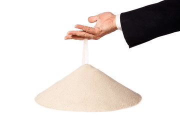 hand of businessman with falling sand on pile