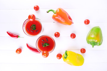 Tomato juice in glasses and fresh vegetables