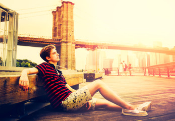 Young adult is sitting next to Brooklyn Bridge