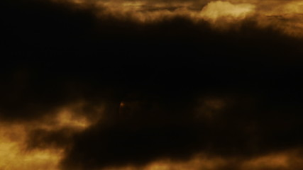 The sun rises on a background of dark clouds. Time-lapse