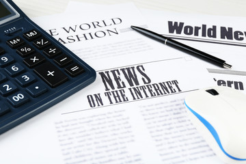 On-line news and business concept. Computer mouse, calculator