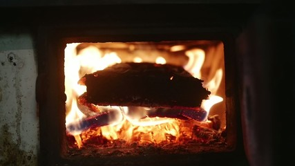 Fire burning under pot full of meat in slow motion