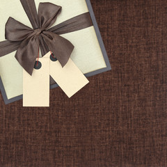 Gift box with ribbon and two blank tags on brown