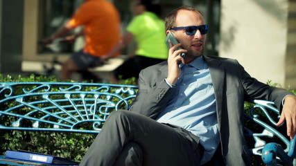Young businessman talking on cellphone in the city
