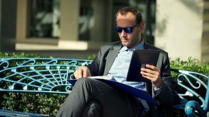 Businessman comparing data on tablet and documents in the city