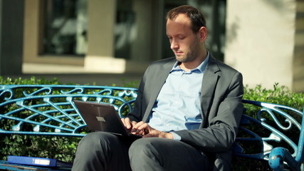 Young businessman working with laptop on the bench in the city