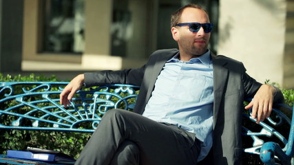 Young, handsome businessman relaxing on the bench in the city