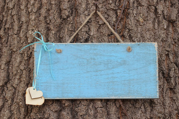 Blank antique blue sign with wood hearts hanging on tree