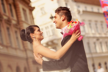 Bride and groom kissing and embracing in the city