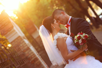 bride and groom kissing at sunset with a flower bouquet