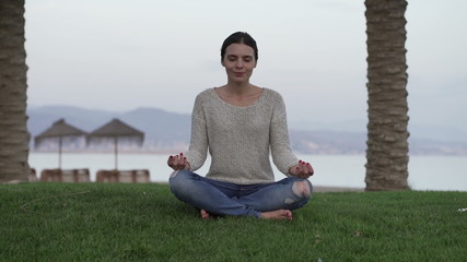 Young, pretty woman meditating on the grass close to the beach