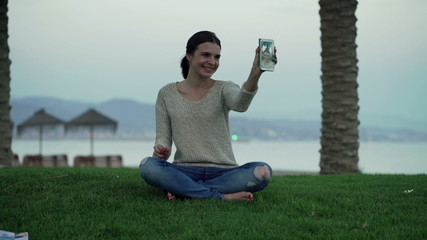 Young woman taking selfie photo with cellphone on the grass