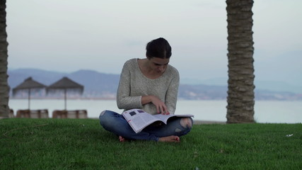 Young woman reading magazine on the grass close to the beach