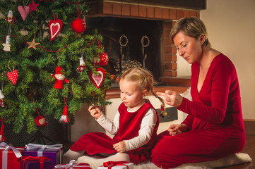 Beautiful blond mother and daughter decorating a Christmas tree.