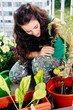 Obrazy na płótnie, fototapety, zdjęcia, fotoobrazy drukowane : Young woman taking care of her little orchard on the balcony