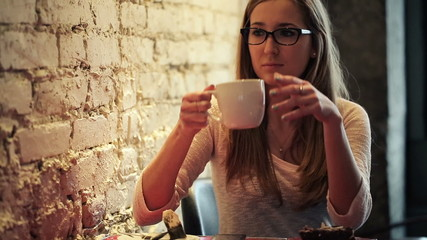 Young, beautiful woman drinking tea  in cafe