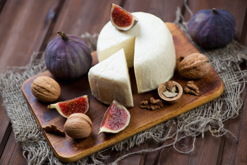Rustic cutting board with figs, cheese and walnuts, studio shot