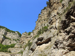 Huge rocks in the narrow gorge against the blue sky. bottom view