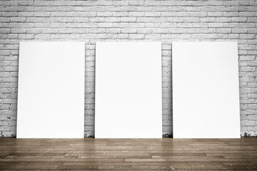 White posters on brick wall and wood floor