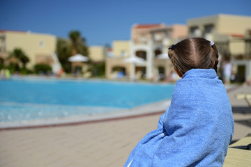Little girl in a blue towel resting near the pool after swimming