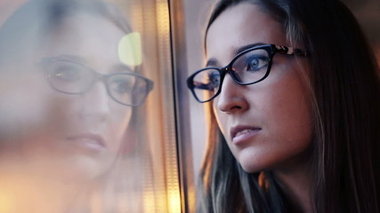 Young, sad woman standing by the window
