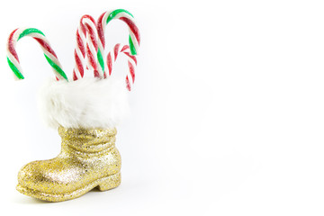 Santas golden boot with candy canes isolated