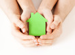 man and woman hands with green paper house