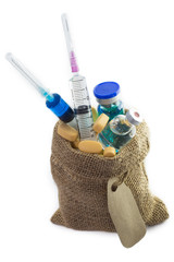 Yellow pills, syringe and ampule in Empty burlap sack with blank