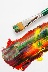 Paintbrush and mixed rainbow oil paints on artist canvas