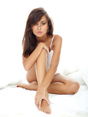 Seductive Woman Sitting on White Bed