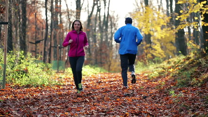 People jogging in autumn forest