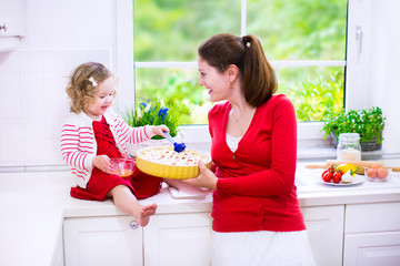 Young mother and cute daughter baking a pie