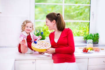 Pretty mother and daughter baking a pie