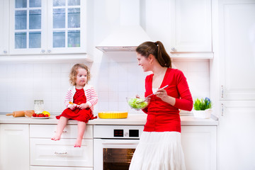 Adorable mother and daughter baking a pie