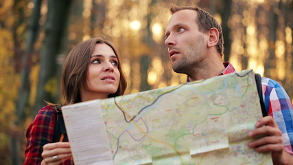 Young couple hikers with a map having quarrel in forest