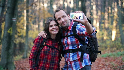 Young couple taking photo with cellphone in autumn forest