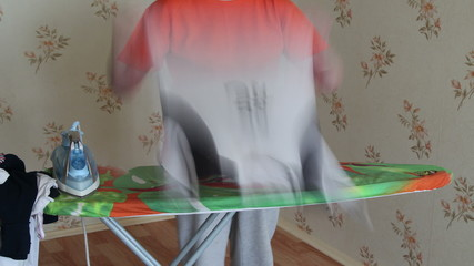 Woman ironing with steam iron at home