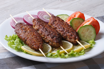 Grilled kebabs on wooden skewers and fresh vegetables