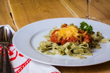 Green herb pasta with bolognese sauce on white plate